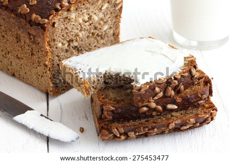 Sunflower seed loaf sliced, cream cheese spread, rustic surface, milk. - stock photo