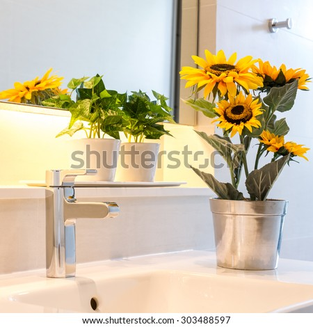 sunflower vase decorated on bathroom sink - stock photo