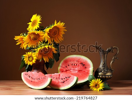 Sunflowers in a vase and fresh watermelon on the table - stock photo