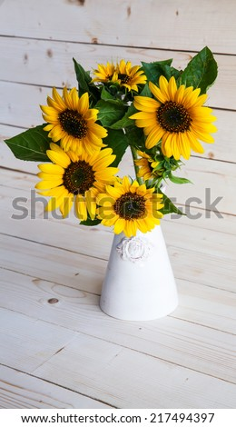 Sunflowers in a vase on a rustic, gray background - stock photo