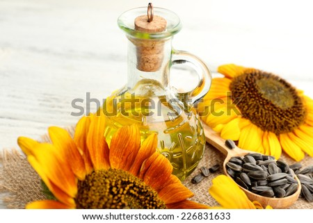 Sunflowers with oil and seeds on wooden background - stock photo