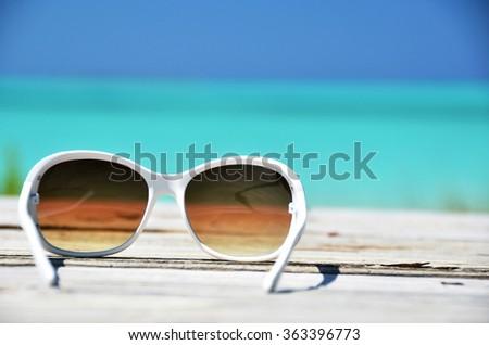Sunglasses against ocean. Exuma, Bahamas - stock photo