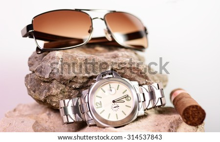 Sunglasses and a cigar laying on a limestone rock - stock photo
