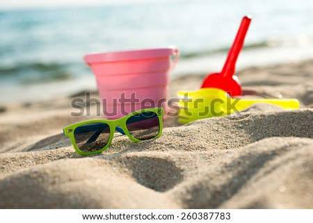 sunglasses and colorful toys for childrens sandboxes at the beac - stock photo
