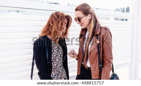 sunglasses and fancy closes are enjoying their walk. One girl with unbounded brown hair is wearing black jacket above motley dress. Another girl is wearing brown leather jacket above titer blouse - stock photo