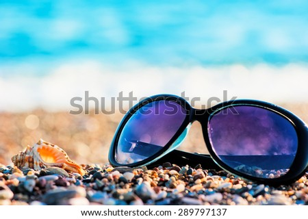 Sunglasses and shells lie on the beach sea - stock photo