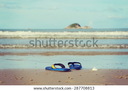 Sunglasses and shoes lay on the sand at the beach, vintage tone - stock photo