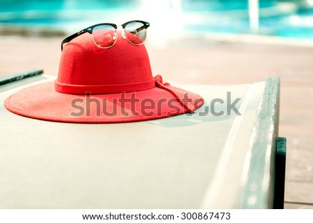 Sunglasses and sunhat at swimming pool - stock photo