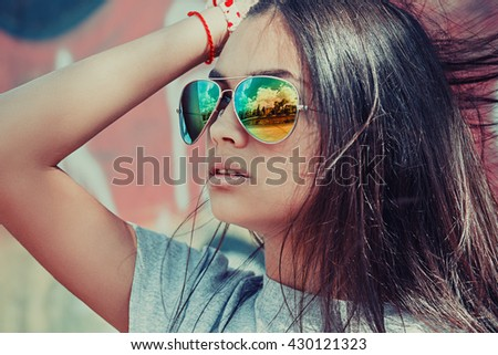 Sunglasses city view reflection. Closeup portrait confident successful beautiful attractive brunette young woman fashion girl model posing, goggles hand on head isolated outdoor red background wall  - stock photo