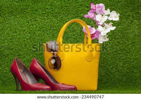 sunglasses, handbag; and red shoes on green grass - stock photo