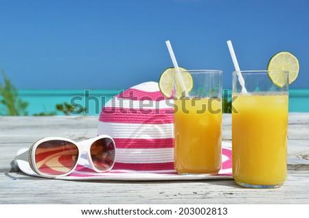 Sunglasses, hat and orange juice  - stock photo