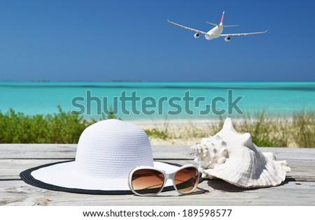 Sunglasses, hat and shell against ocean. Exuma, Bahamas - stock photo
