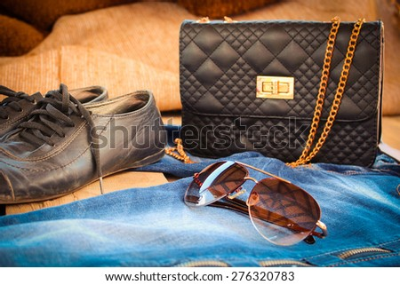 Sunglasses, jeans, handbag and shoes. Toned image. - stock photo