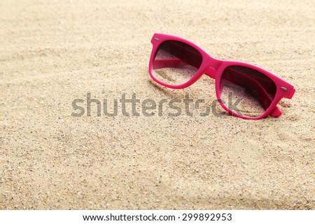 Sunglasses on a beach sand - stock photo