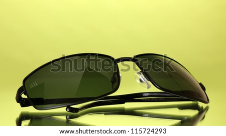 Sunglasses on green background - stock photo