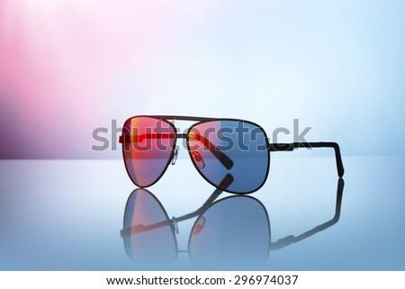 Sunglasses on reflective surface. - stock photo