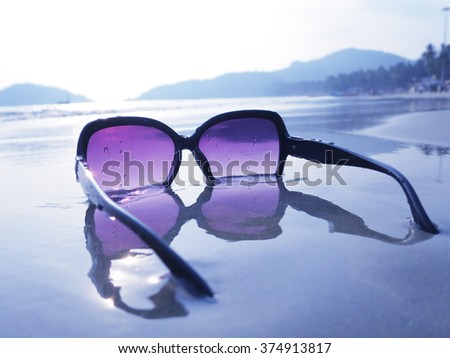 Sunglasses on the sand of Palolem beach. South Goa, India - stock photo