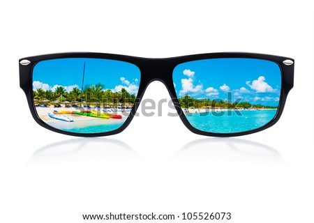 Sunglasses  with a tropical beach and sailing boats reflected where the lenses should have been isolated on white - stock photo