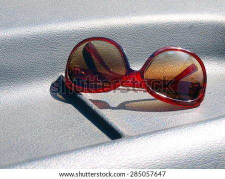 Sunglasses with brown glasses and red plastic frame on black leather car front window panel - stock photo