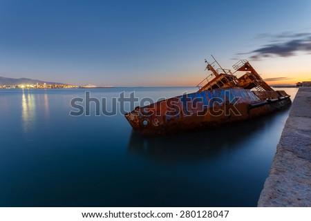 Sunken fishing ship below water, abandoned in the dock near Piraeus in Greece - stock photo