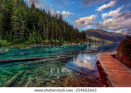 Sunken logs in a crystal clear mountain lake with evergreen trees and a wooden walkway - stock photo