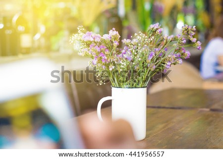 Sunlight beam with vintage flowers on wooden in cafe background, Bouquet flower - stock photo