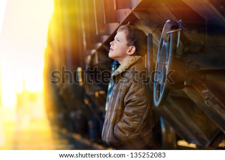 sunlight boy bum blonde in brown jacket and crumpled jeans on street near car look up - stock photo
