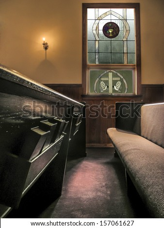 sunlight falls across pews in a small church from stained glass window and light of small wall - stock photo
