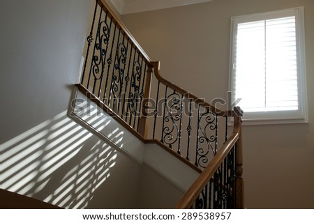 Sunlight from an open window with blinds shines onto stairway creating diagonal lines on wall. - stock photo