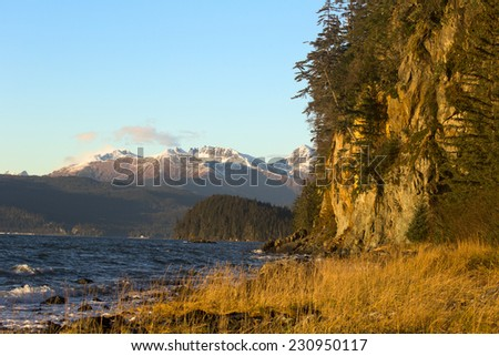 Sunlight highlights autumn colors of Fritz Cove on coast of Douglas Island, Juneau, Alaska; blue waters of Stephens Passage and mountains enhance; copy space in blue sky of horizontal image;  - stock photo