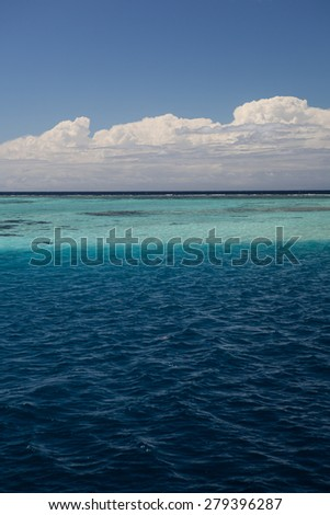 Sunlight highlights the colors of a shallow reef and lagoon in the Solomon Islands.  - stock photo