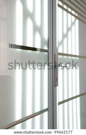 sunlight on the glass door with metal trim and metal handle - stock photo