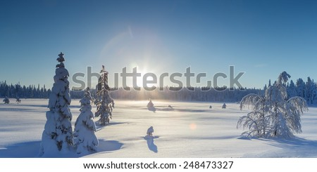 Sunlight over a winter landscape at Finland - stock photo