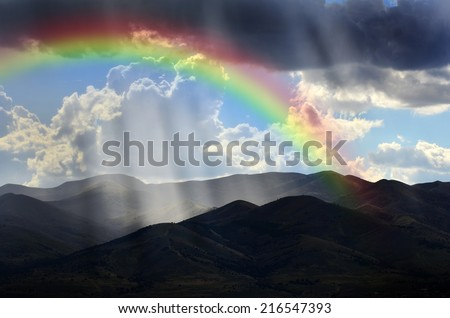 Sunlight rays from clouds falling on dark mountain range with Rainbow - stock photo