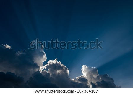 sunlight rays to the storm clouds on blue sky - stock photo