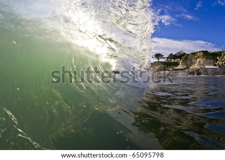 Sunlight shines through a breaking wave on the shoreline. - stock photo