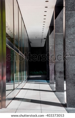 Sunlight streams through this contemporary building walkway in New York City. - stock photo