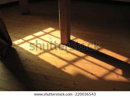 Sunlight streams through window onto wooden floor. - stock photo