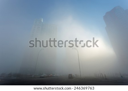 sunlight through the fog on the morning city street - stock photo