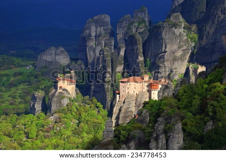 Sunlit monastery of Roussanou and dark clouds in the background, Meteora, Greece - stock photo
