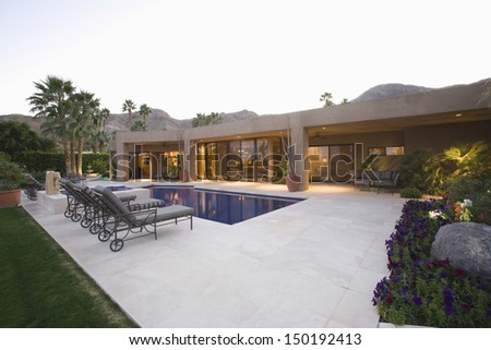 Sunloungers along the pool against modern house and clear sky - stock photo
