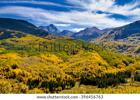 Sunny autumn afternoon view of Capitol Peak near Aspen Colorado surrounded by valley filled with changing yellow Aspen trees and blue sky with wispy clouds - stock photo
