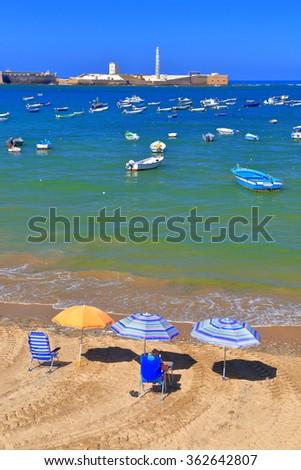 Sunny beach on the Atlantic ocean with San Sebastian Castle in the background, Cadiz, Andalusia, Spain - stock photo