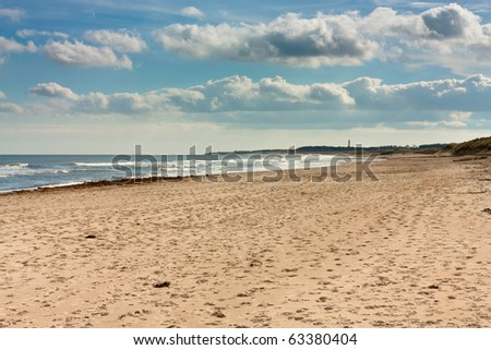 Sunny beach with blue sky, clouds and breaking waves on Northumberland coast, North East England. - stock photo