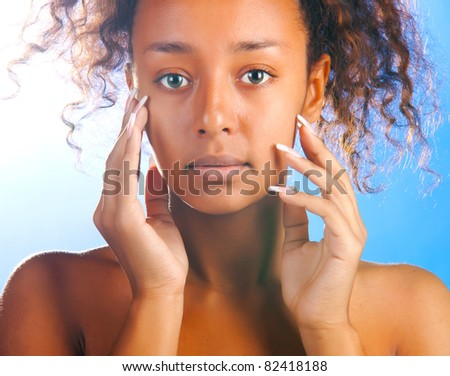 sunny beautiful woman with is touching her face and looking at camera on sky background - stock photo