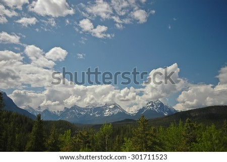 sunny blue sky and snow mountain - stock photo