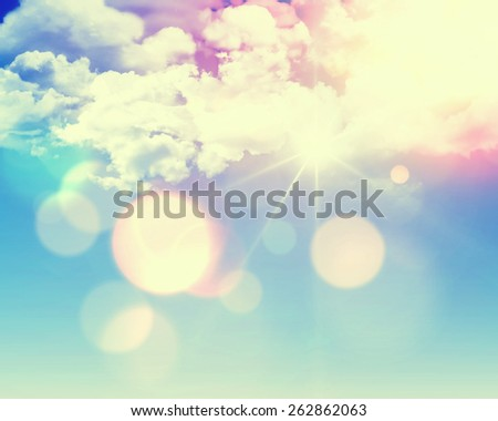 Sunny blue sky background with fluffy white clouds and retro effect added - stock photo