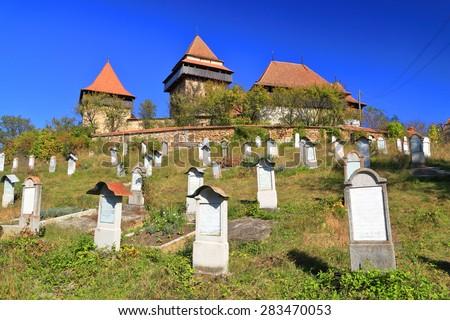 Sunny cemetery and distant church with medieval architecture on UNESCO world heritage list, Viscri, Transylvania, Romania - stock photo