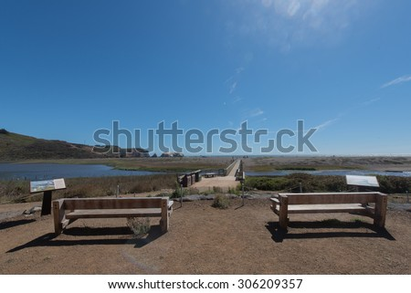 Sunny day at the beach with two benches facing a walkway and the main beach - stock photo