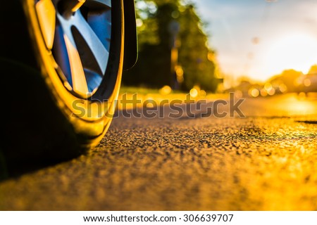 Sunny day in a city, headlights of approaching cars, the view from the road level from the wheel of the car - stock photo